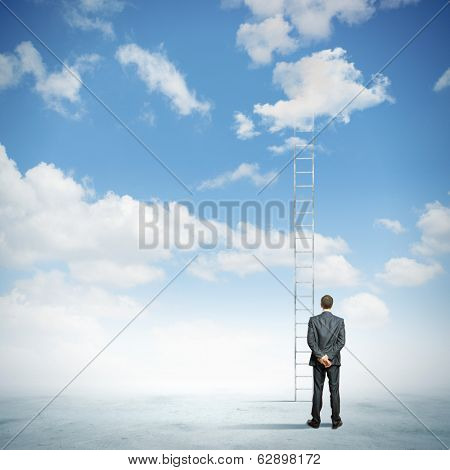 Rear view of businessman standing near ladder going high in sky