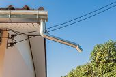 stock photo of downspouts  - on a roof hangs a drainpipe next to a tree - JPG