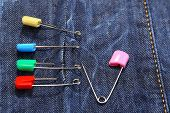 Safety pins on fabric background