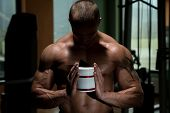foto of muscle builder  - Body builder Posing With Supplements For Copy Space - JPG