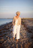 pic of stroll  - Image of senior woman walking on the beach - JPG