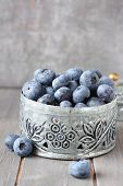 stock photo of casket  - Fresh blueberries in small delicate metal casket on wooden background - JPG