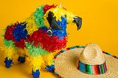 stock photo of pinata  - A mexican torro pinata and sombrero on a yellow background - JPG