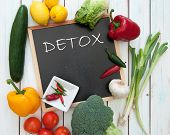 stock photo of minerals  - Detox handwritten on a chalkboard surrounded by fresh vegetables - JPG