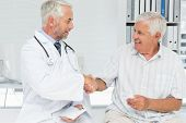 image of medical office  - Smiling senior patient and doctor shaking hands in the medical office - JPG