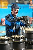 adult industrial worker during heavy industry machinery assembling on production line manufacturing