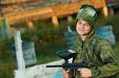 picture of paintball  - Happy paintball sport player man in protective camouflage uniform and mask with marker gun outdoors - JPG