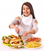 stock photo of high calorie foods  - Woman eating fast food - JPG