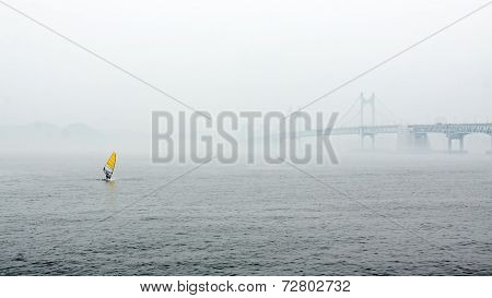 Misty river landscape with bridge and yellow sail