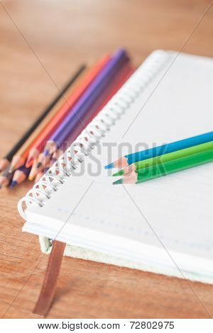 Colorful Pencils On Spiral Notebook And Green Notebook