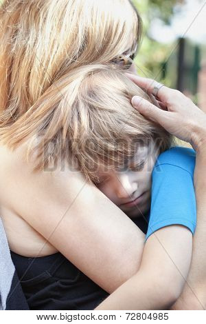 Boy Embracing His Mother, Sitting On Her Lap Sleeping