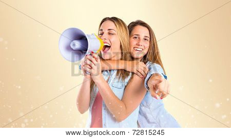 Girls Shouting With Megaphone Over Ocher Background