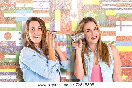 Friends Talking Through A Tin Phone Over Flags Background