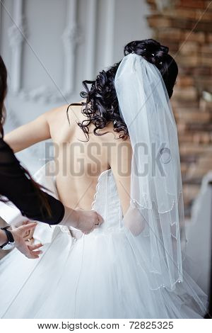 To the bride help to clasp a wedding dress