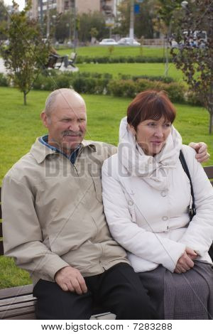The Man And The Woman Sit On A Bench In Park And Look Aside