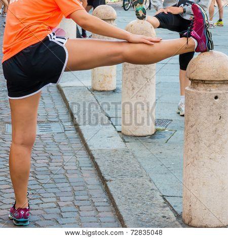 Girl Stretching Before Running In City Marathon