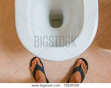 Man's Flip-flops Feet In Front Of Water Closet