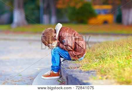 Upset Kid Boy Sitting Alone In City Park
