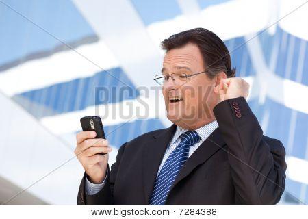 Empresário olhando celular rebita seu punho em alegria