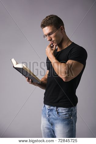 Handsome Sexy Muscular Man Reading Big Book On Grey