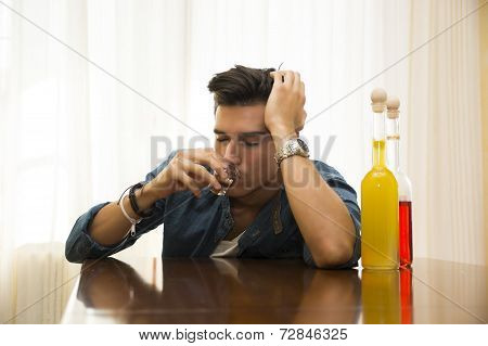 Sleepy, Drunk Young Man Sitting Drinking Alone At A Table With Two Bottles