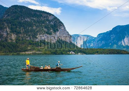 People Crossing The Lake With A Traditional Boat