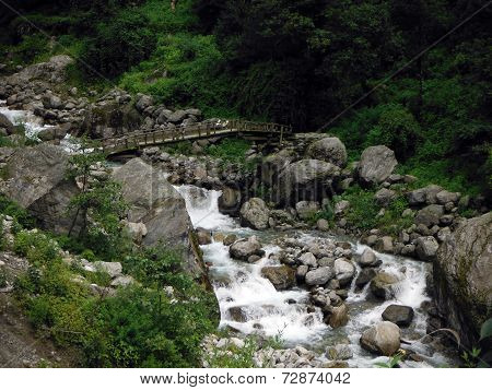 Makeshift Wooden Bridge Crossing A Mountain River