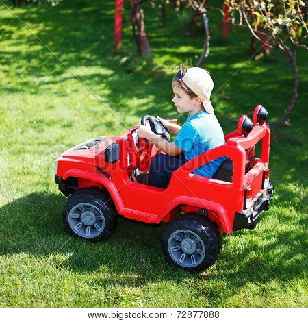 Little Boy Drive Electrical Vehicle In Garden