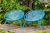 foto of lawn chair  - Blue garden metal chairs with leaves and wooden fence - JPG