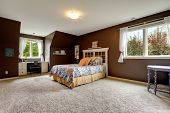 stock photo of master bedroom  - Spacious master bedroom interior with soft carpet floor and dark brown walls - JPG