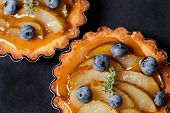 picture of tarts  - Homemade pear and blueberry tarts on black background - JPG
