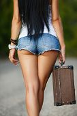 stock photo of lonely  - Pretty young woman hitchhiking along a road - JPG