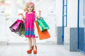 stock photo of curio  - Cheerful preschool girl walking with shopping bags - JPG