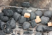 stock photo of briquette  - Lighting the fire of charcoal  - JPG