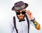 image of bowing  - young hipster man wearing hat suspenders a bow - JPG