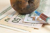 foto of opiate  - Dead apple with syringe on dollars  - JPG