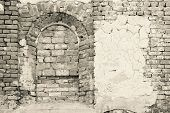picture of niche  - arch niche and the destroyed plaster on an old brick wall of the ancient building in monochrome tones - JPG