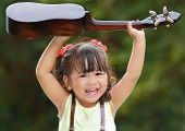 image of ukulele  - Little asian girl was smile and playing ukulele happily in the park