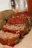 picture of meatloaf  - Sliced meatloaf on a wood cutting board with baked potatoes  - JPG