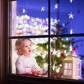 pic of cute bears  - Cute curly toddler girl sitting with a toy bear at home during Xhristmas time preparing to celebrate Xmas Eve view through a window from outside into a decorated dining room with tree and lights - JPG