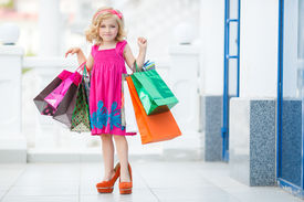 image of curio  - Cheerful preschool girl walking with shopping bags - JPG