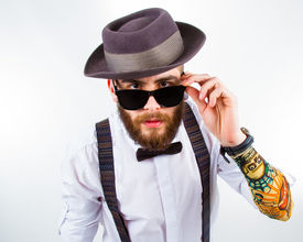 stock photo of suspenders  - young hipster man wearing hat suspenders a bow - JPG