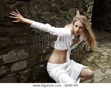 girl standing near a stone wall
