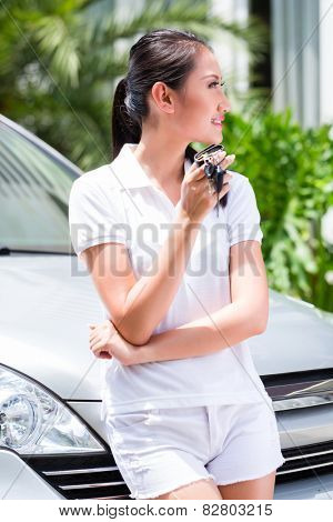 Asian woman showing key of new car