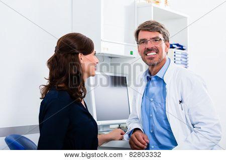 General practitioner in doctors office seeing patient
