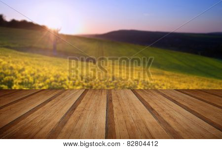 Beautiful Sunrise Over Field Of Rapeseed In Countryside In Spring With Wooden Planks Floor