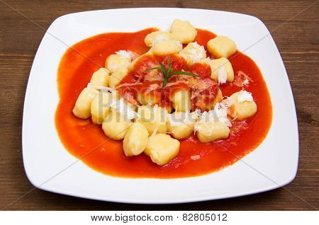 Gnocchi with tomato sauce on wood