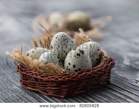 quail eggs in a wicker basket on a gray wooden background