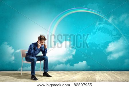 Troubled young man sitting in chair outdoors