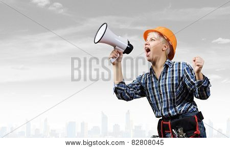 Young emotional woman builder screaming in megaphone